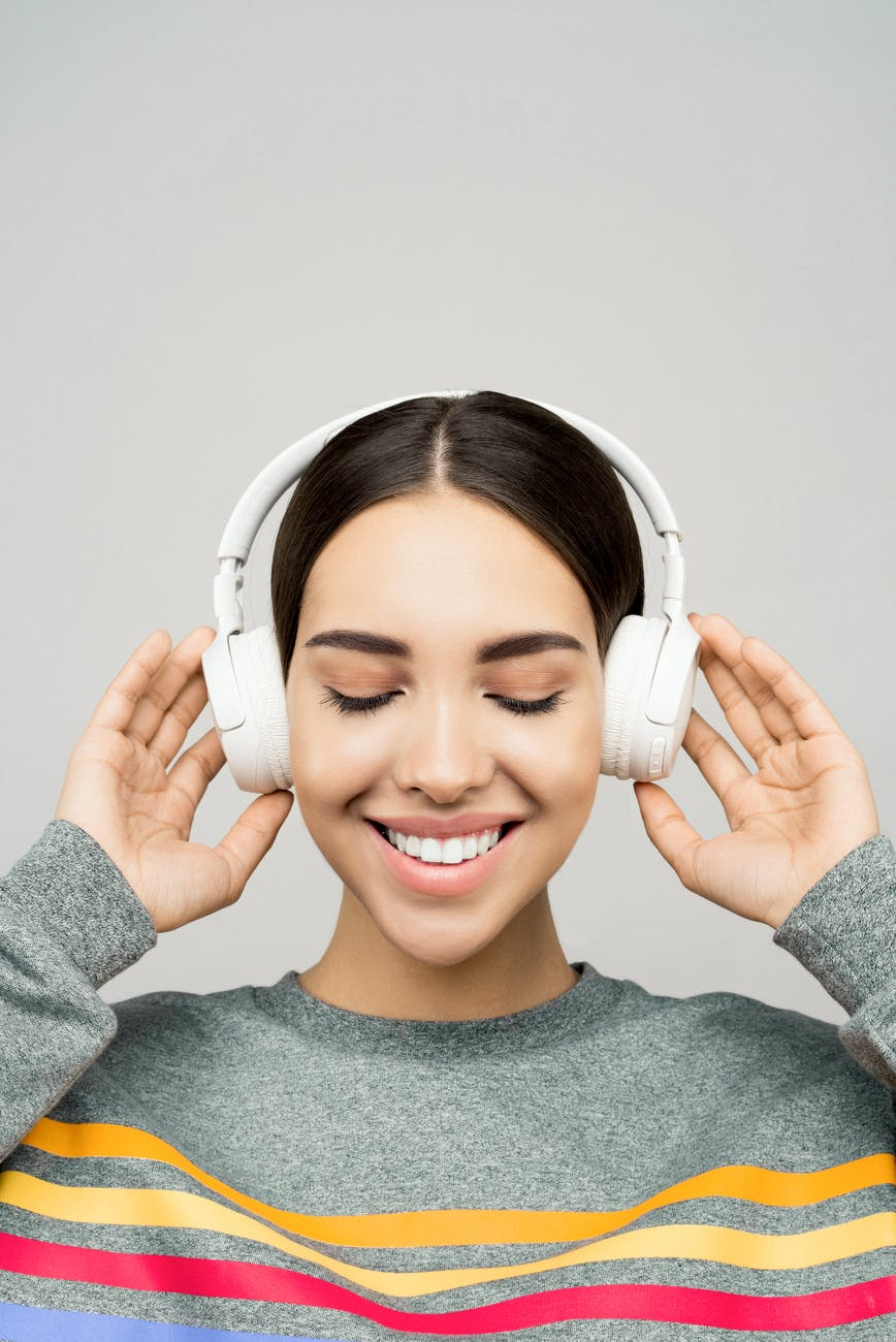 woman in gray sweater wearing white headphones
