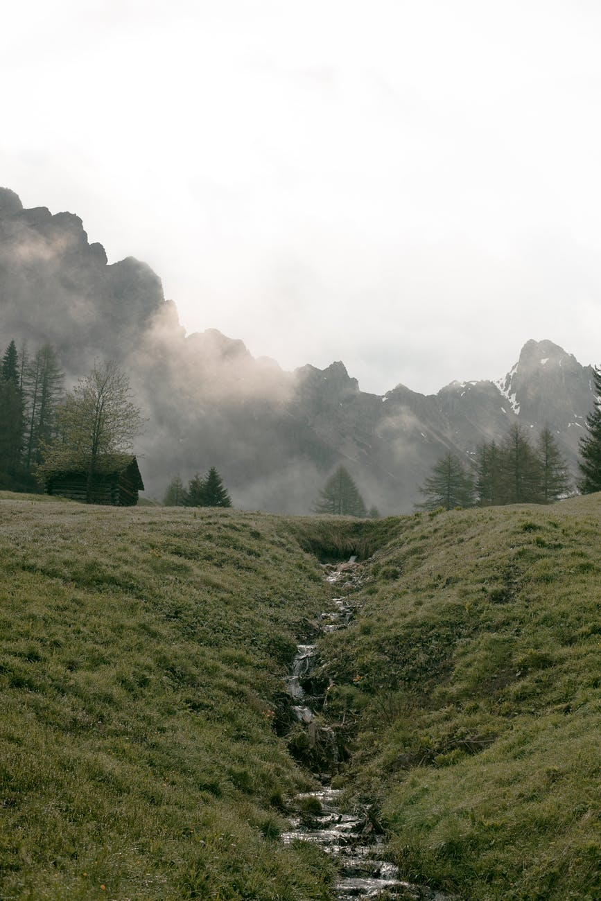 lonesome house on foggy valley against massive mountain ridge