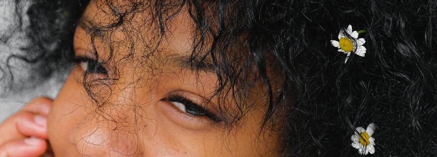 romantic black woman with chamomiles in hair