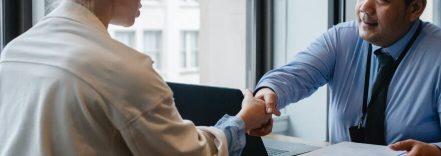 ethnic businessman shaking hand of applicant in office