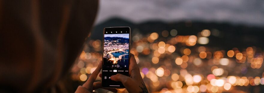 crop unrecognizable person taking photo of night city on smartphone