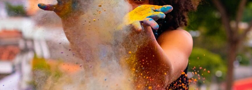 unrecognizable black woman creating colorful dust during holi on embankment