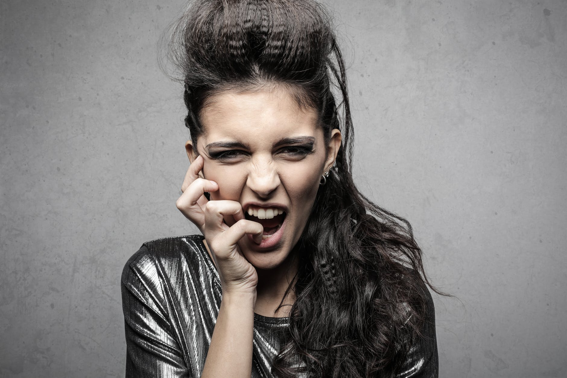 stylish female rocker screaming in studio