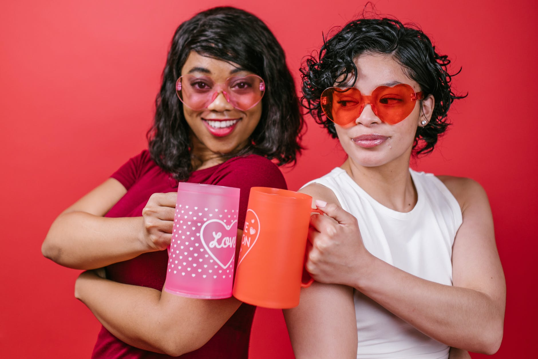 two women holding pink and red mugs