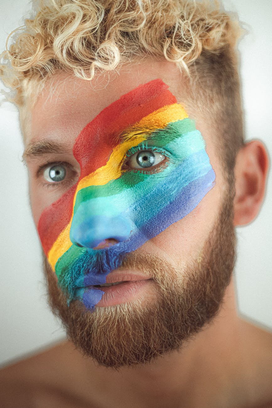 crop young man with lgbt flag painted across face