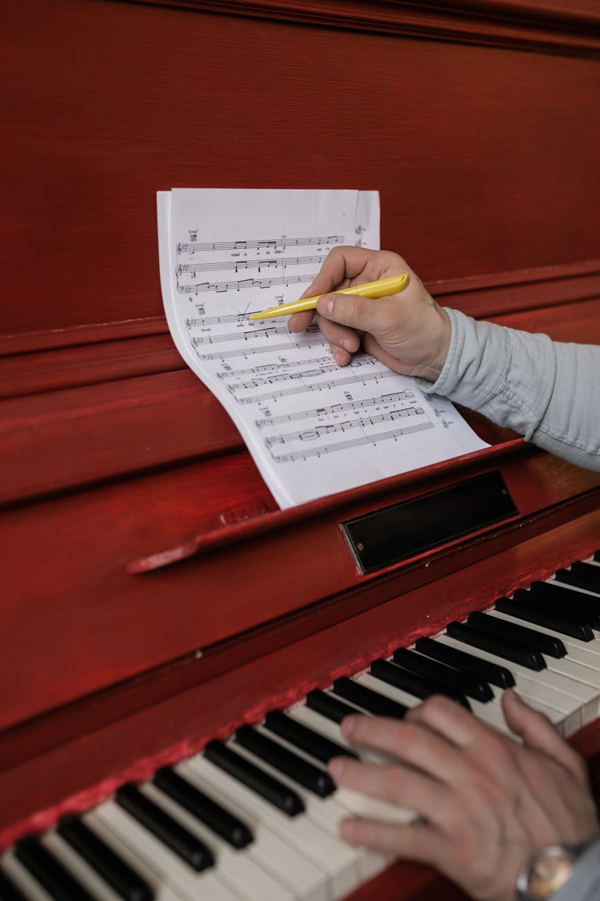 person writing on the sheet music