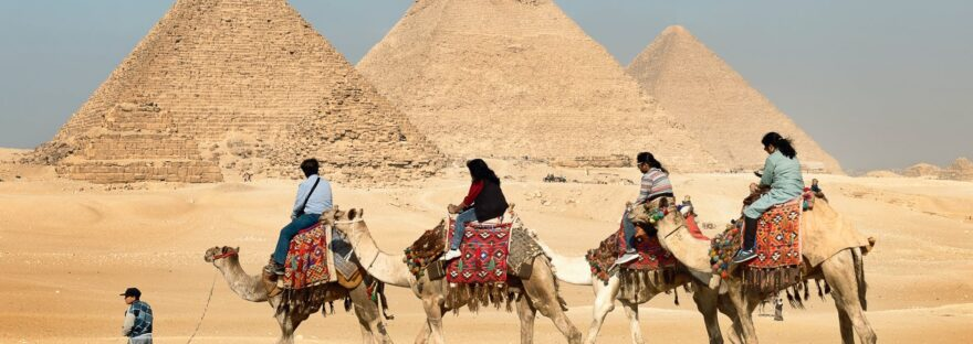 four people riding on camels across the pyramids