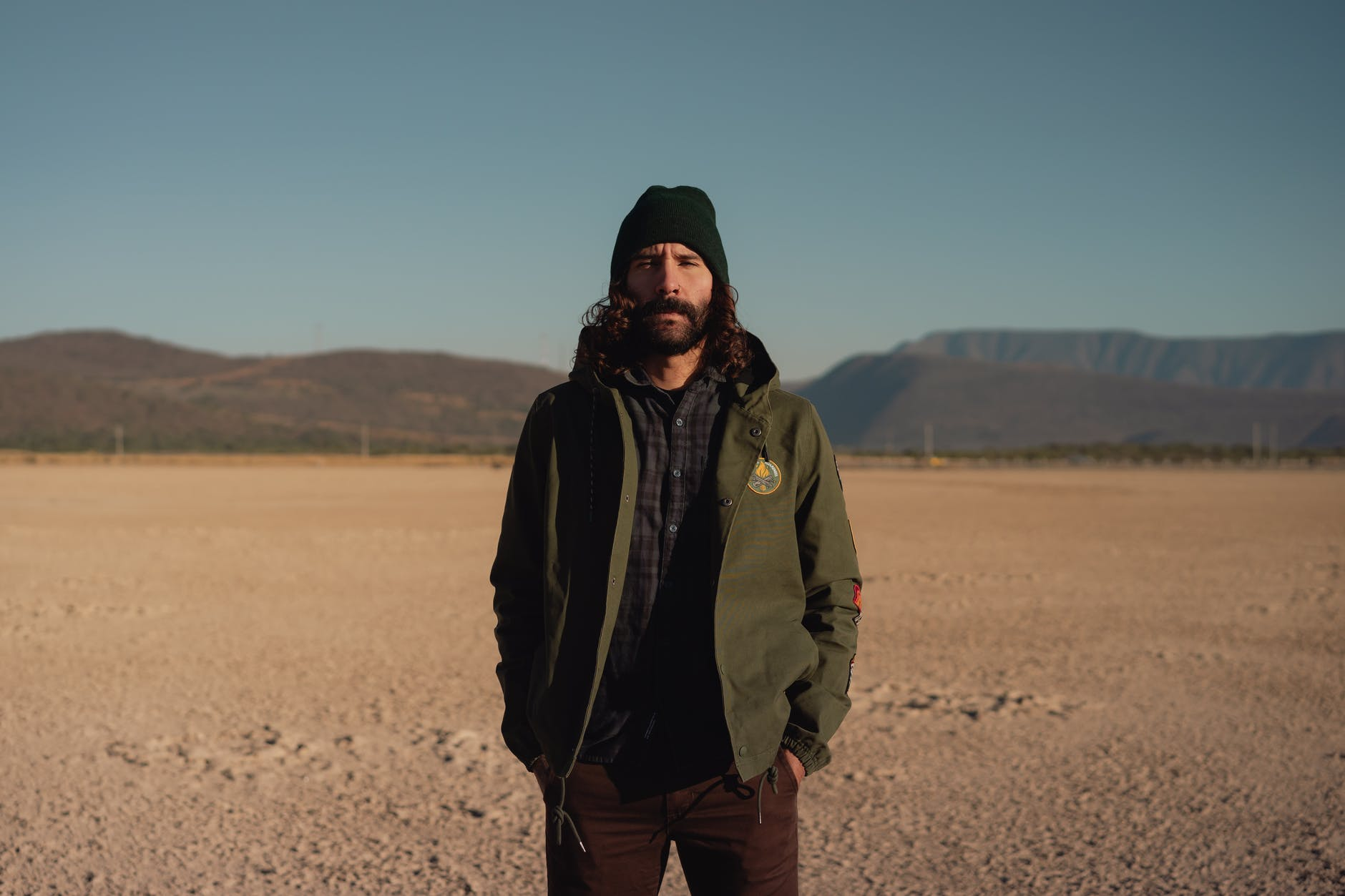 bearded man standing in desert valley surrounded by hills