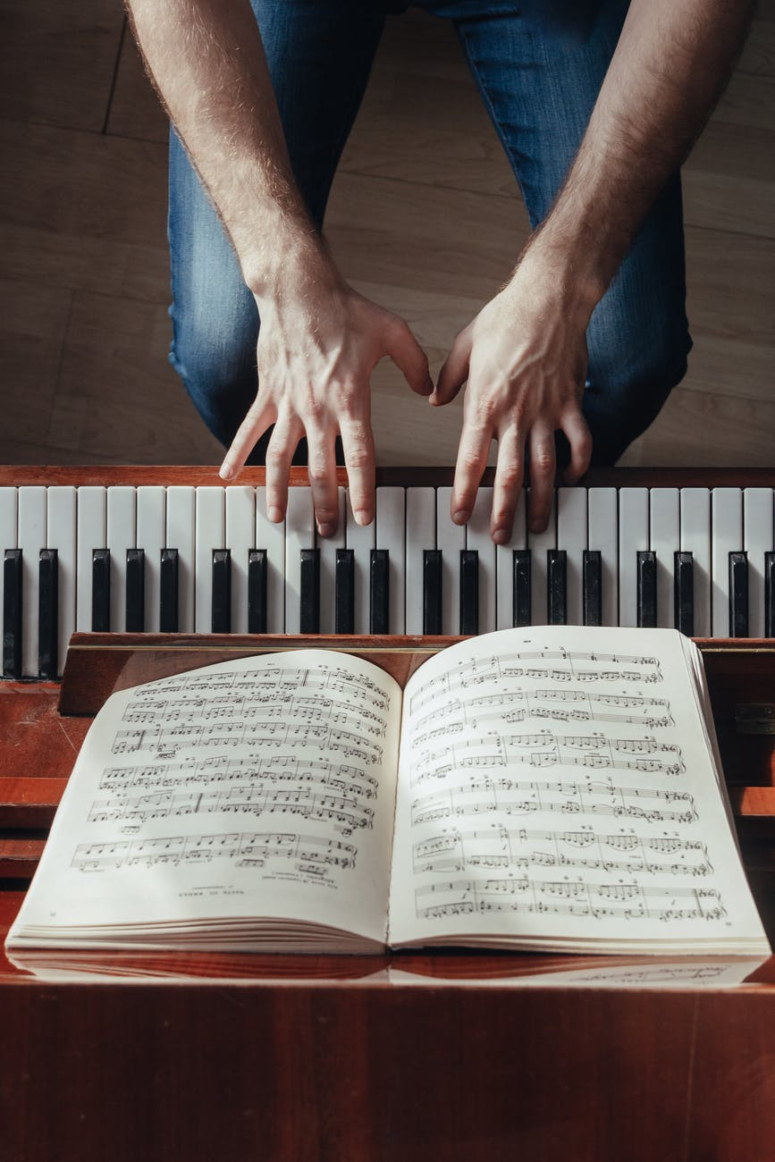crop pianist playing piano with sheet music on stand